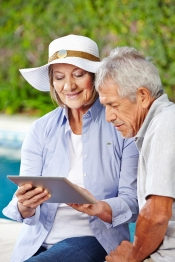 Senior couple looking at tablet computer outdoors at pool