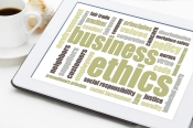 business ethics word cloud on a digital tablet with a cup of cof