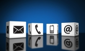 Web contact us and Internet connection concept with email mobile phone and at icons and symbol on cubes with reflection and blue background for website blog and on line business.